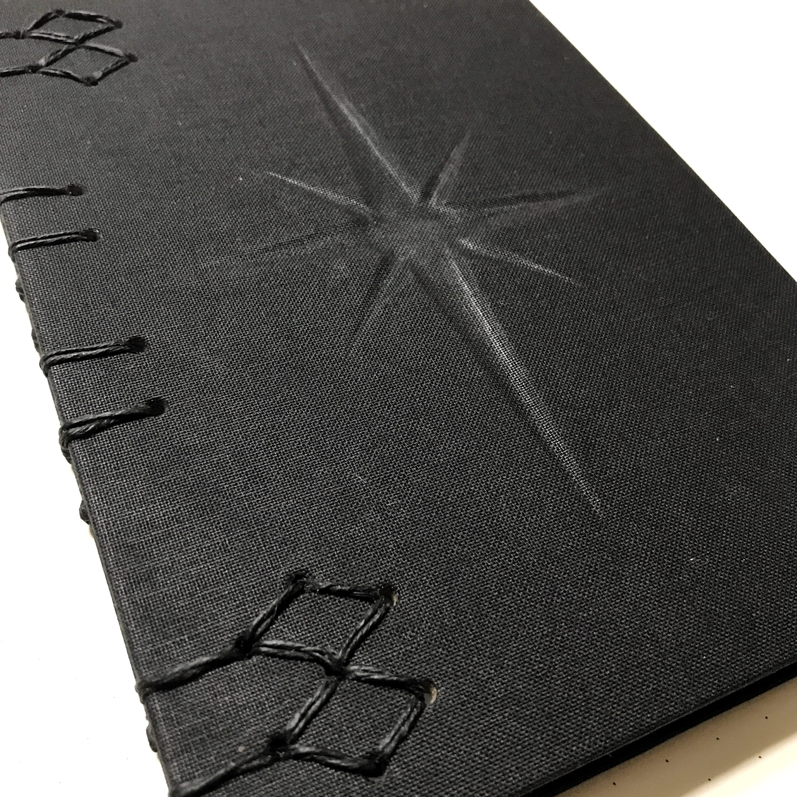 Closeup of journal with black cover and embossed compass design