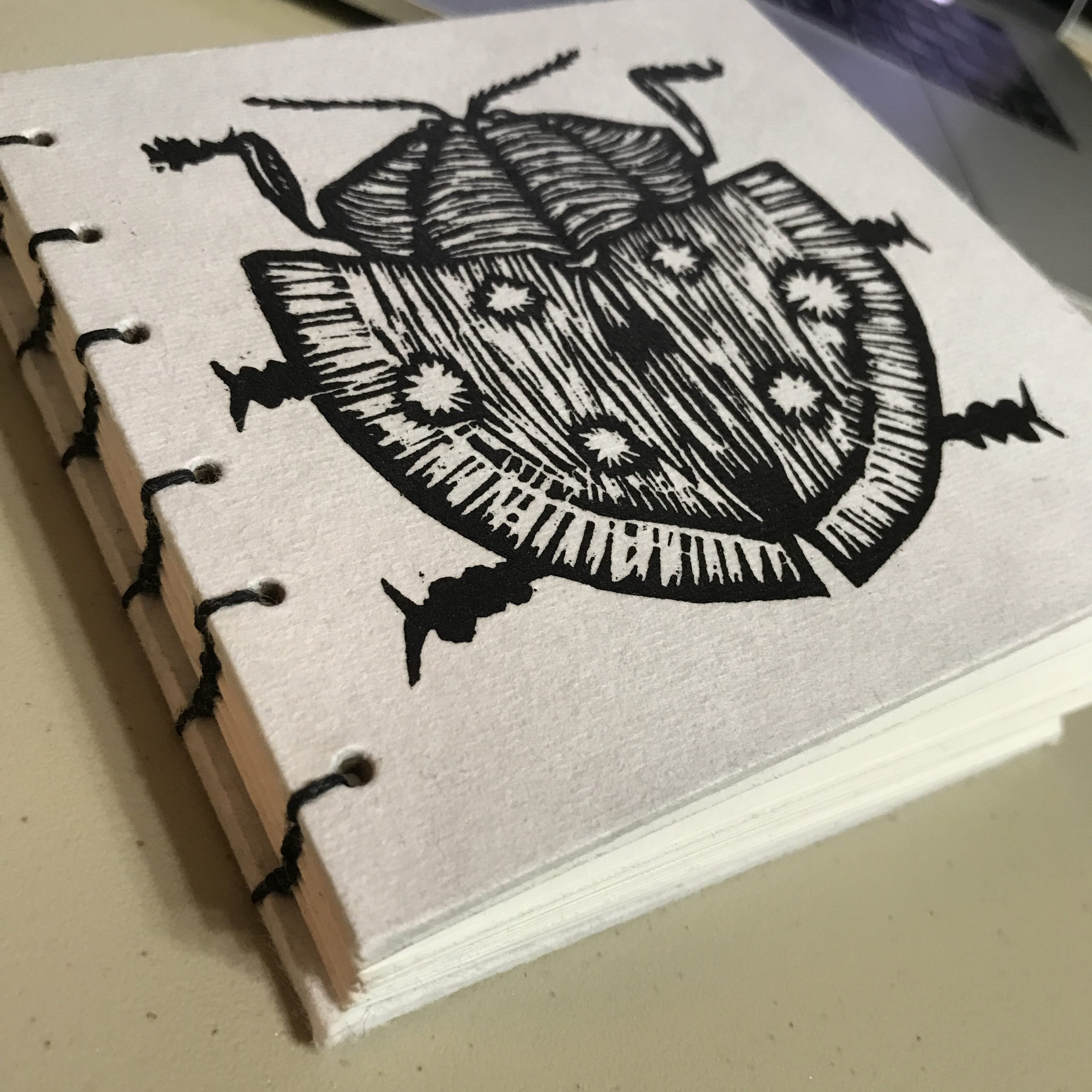 Sketchbook with bug linocut on cover
