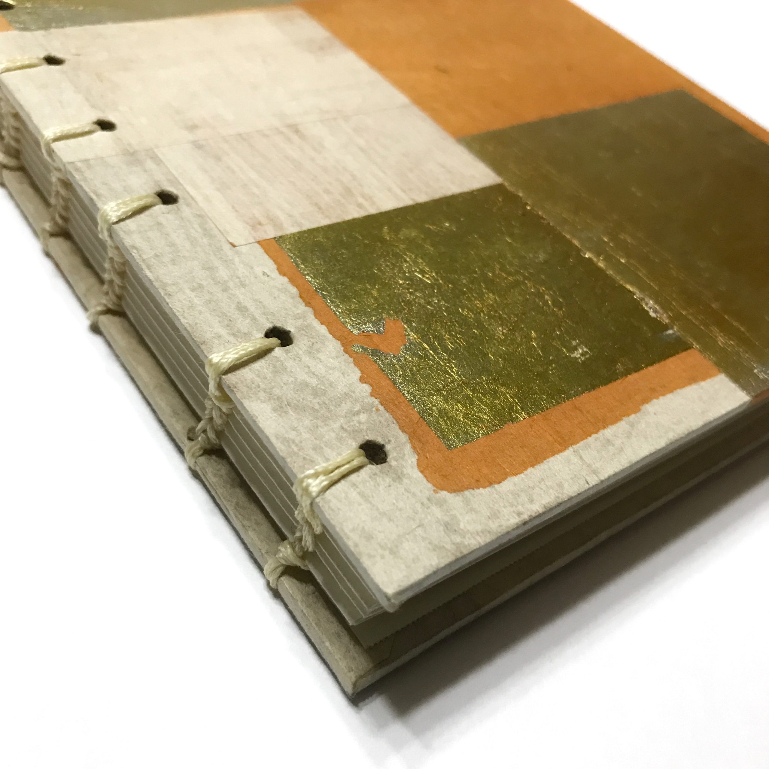 Closeup of cover of sketchbook with gold leaf and orange design